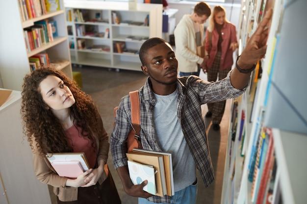 Wysoki kąt portretowania dwóch uczniów zdejmujących książki z półki w szkolnej bibliotece,