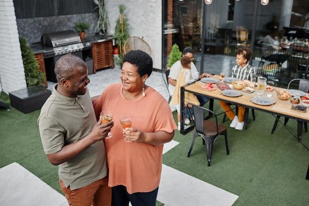 Wysoki kąt portretu dojrzałej pary z afryki rozmawiającej podczas rodzinnego spotkania na zewnątrz...