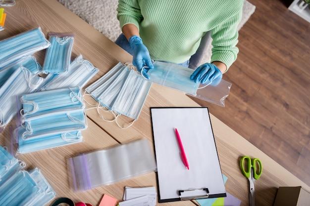Wysoki kąt powyżej widoku zdjęcia damskich rękawiczek lateksowych zorganizuj zamówienie masek na grypę na twarz wyślij klienta przygotuj dostawę bezpieczne antywirusowe włóż maski oddechowe do torby na suwak pozostań w biurze domowym w pomieszczeniu