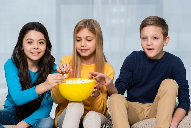 Wysoki kąt przyjaciół jeść popcorn