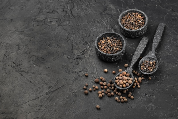 Wysoki kąt przypraw i nasion w miskach z łupkiem