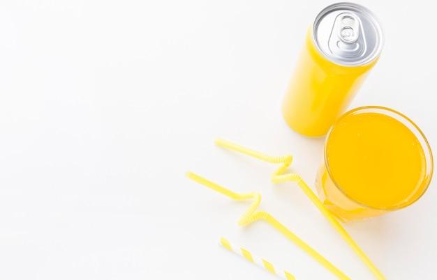 Wysoki kąt puszki na napoje bezalkoholowe ze szklanką i słomkami