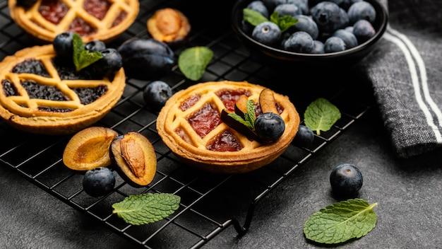Wysoki kąt pysznych ciast ze śliwkami na stojaku do chłodzenia