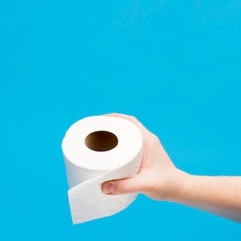 Wysoki kąt ręki trzymającej rolkę papieru toaletowego