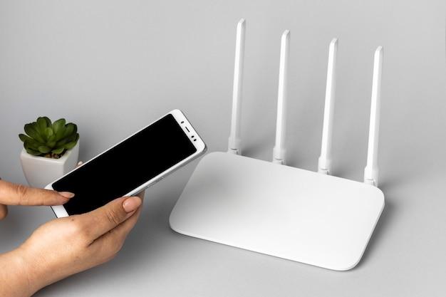 Wysoki kąt routera wi-fi z rękami trzymającymi smartfon i roślin