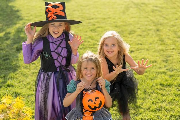 Wysoki kąt ślicznych małych dziewczynek z kostiumami na halloween