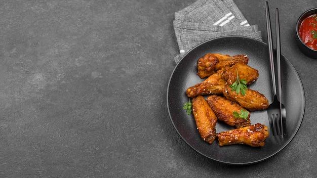 Wysoki kąt smażonego kurczaka na talerzu z sosem i miejsca na kopię