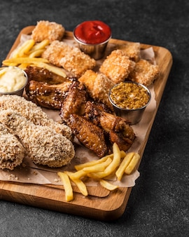 Wysoki kąt smażonego kurczaka z bryłkami i frytkami