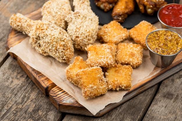 Wysoki kąt smażonego kurczaka z bryłkami i różnymi sosami