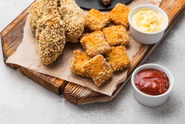 Wysoki kąt smażonego kurczaka z dwoma różnymi sosami i bryłkami
