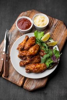Wysoki kąt smażonego kurczaka z sosem i surówką