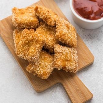 Wysoki kąt smażonych bryłek kurczaka z sosem