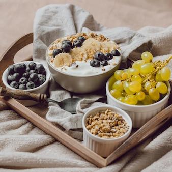 Wysoki kąt śniadanie w łóżku ze zbożami i winogronami