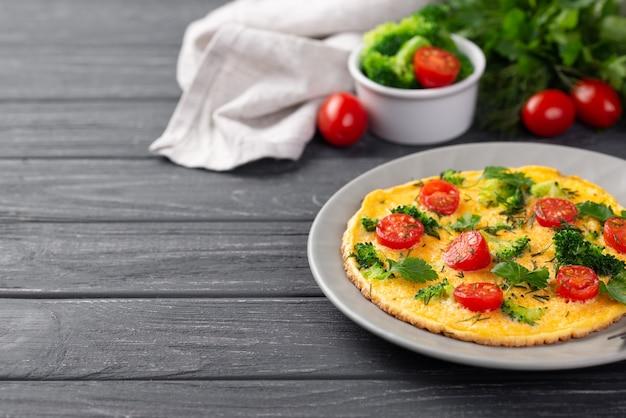 Wysoki kąt śniadaniowego omletu na talerzu z pomidorami i brokułami