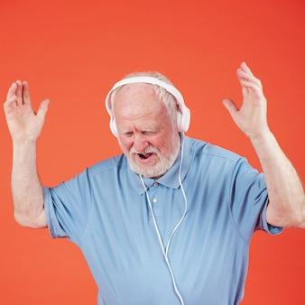 Wysoki kąt starszy mężczyzna słuchania muzyki