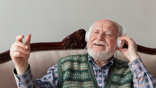Wysoki kąt starszy na kanapie słuchania muzyki