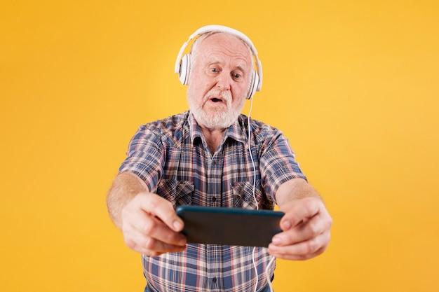 Wysoki kąt starszy odtwarzanie muzyki na telefon