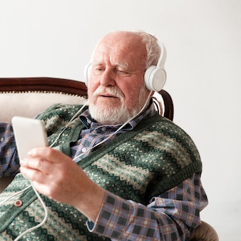 Wysoki kąt starszy odtwarzanie muzyki na telefonie komórkowym