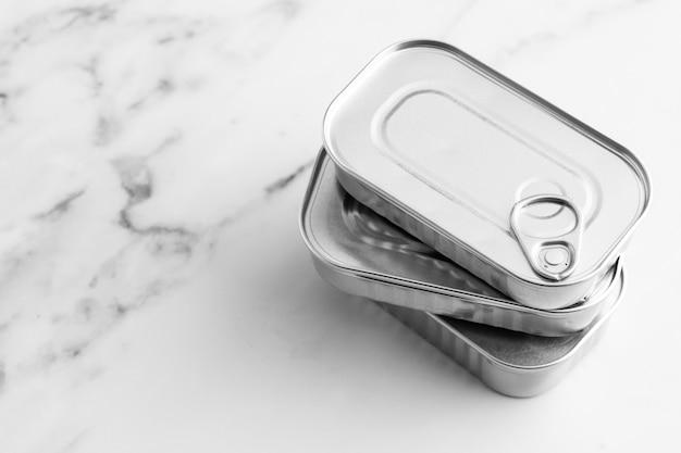 Wysoki kąt stosu srebrnych puszek na marmurowym blacie