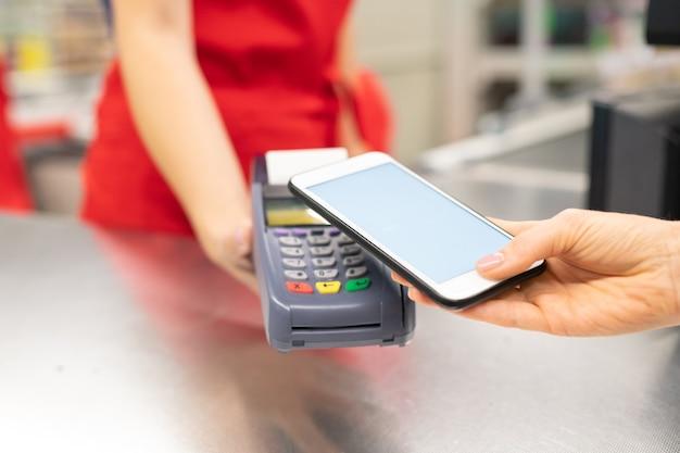 Wysoki kąt strzał z bliska nierozpoznawalnej młodej kobiety korzystającej z technologii bankowości internetowej na smartfonie, aby zapłacić za towary w sklepie