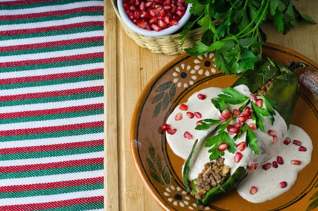 Wysoki kąt strzału chiles en nogada w płycie na drewnianej desce na stole