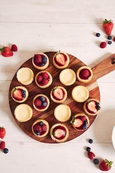 Wysoki kąt strzału cupcakes sera z galaretką owocową i owocami na drewnianej tablicy