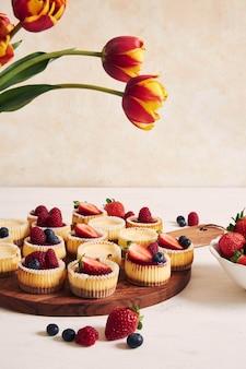 Wysoki kąt strzału cupcakes sera z galaretką owocową i owocami na drewnianym talerzu