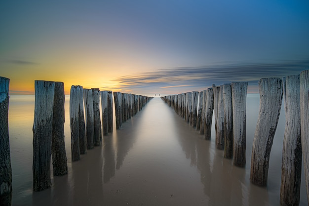Wysoki kąt strzału drewnianego pokładu na brzegu morza, prowadzącego do morza o zachodzie słońca