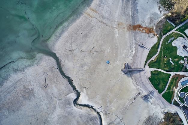 Wysoki kąt strzału dużego pęknięcia na kamienistym brzegu obok turkusowej wody