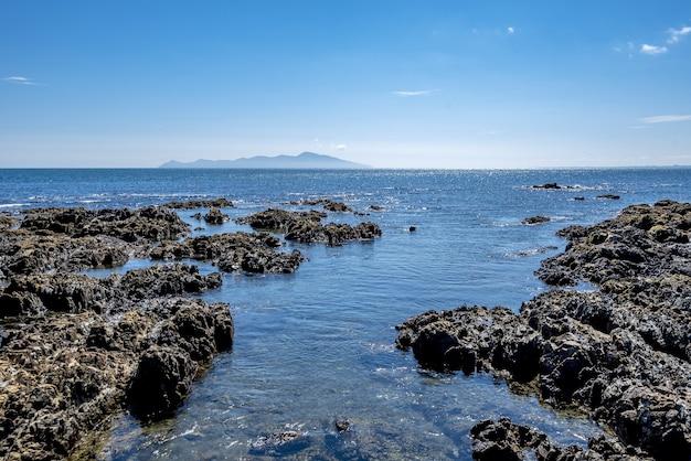 Wysoki kąt strzału formacji skalnych w wodzie zatoki pukerua w nowej zelandii