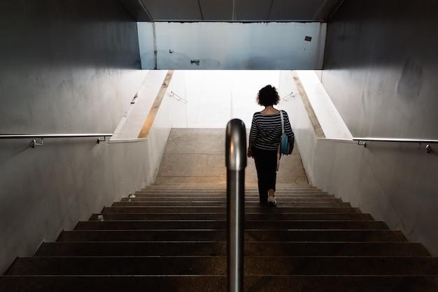 Wysoki kąt strzału kobiety idącej po schodach na pustej klatce schodowej