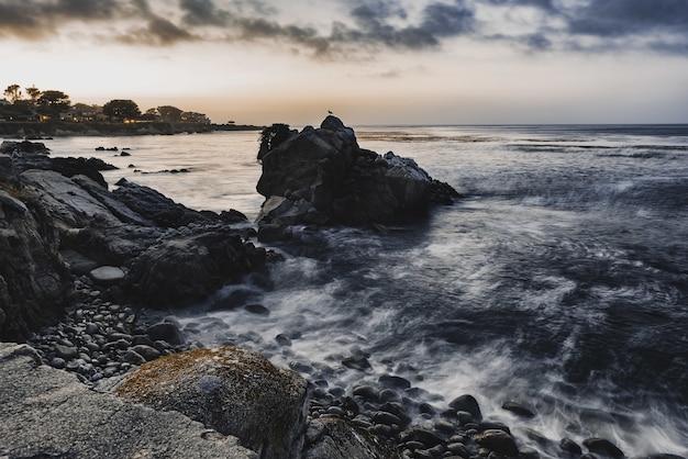 Wysoki kąt strzału małych skał na brzegu morza pod zachmurzonym niebem wieczorem