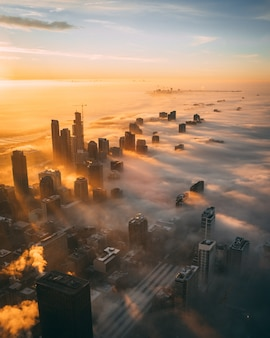 Wysoki kąt strzału miasta z wysokimi drapaczami chmur podczas zachodu słońca pokryte białymi chmurami