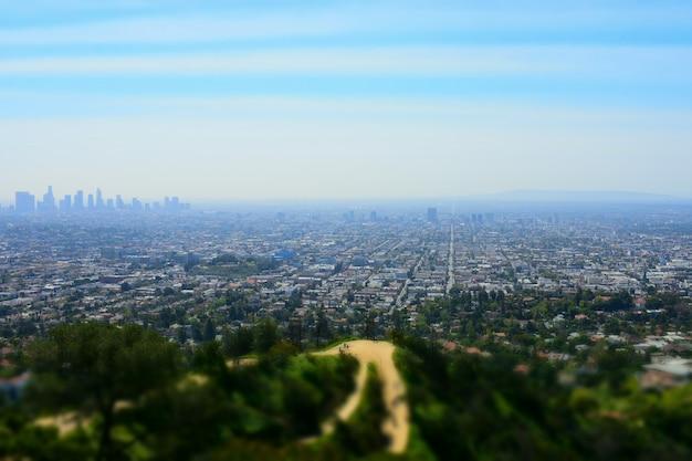 Wysoki kąt strzału miejskiego widoku z wieżowcami otoczonymi zieloną scenerią