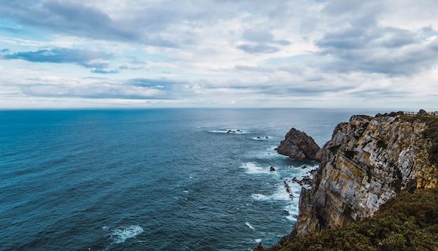 Wysoki kąt strzału morza w pobliżu góry pod zachmurzonym niebem w cabo penas, asturia, hiszpania