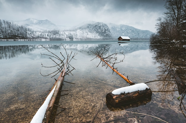 Wysoki kąt strzału na spokojne jezioro ze wzgórzami pod mglistym niebem