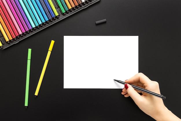 Wysoki kąt strzału osoby rysującej na białym papierze z kolorowymi piórami na czarnej powierzchni
