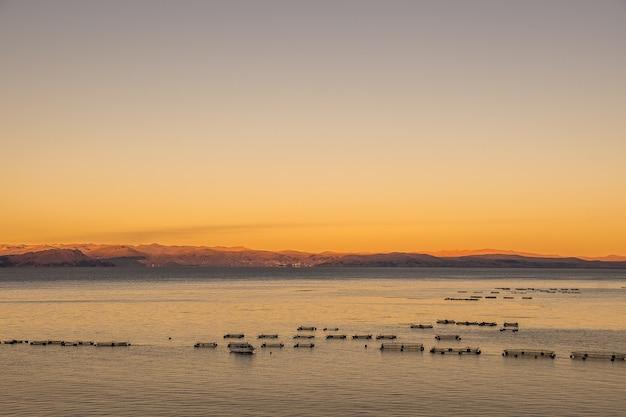 Wysoki kąt strzału spokojnej powierzchni oceanu z górami