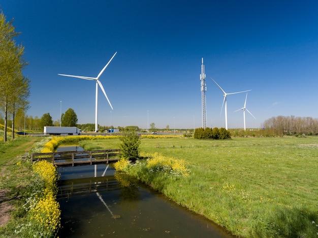 Wysoki kąt strzału turbin wiatrowych w pobliżu autostrad i łąk zrobionych w holandii