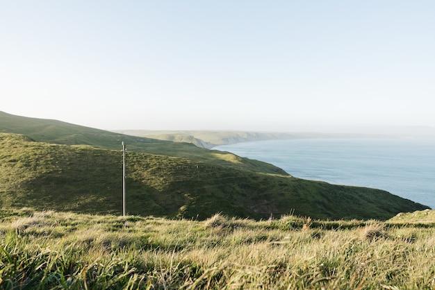Wysoki kąt strzału wzgórz pokrytych zielenią otaczającą ocean