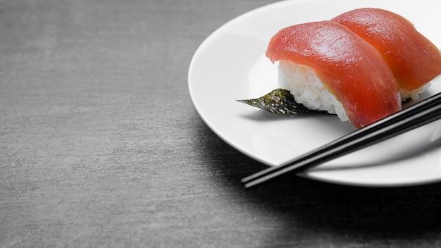 Wysoki kąt surowej ryby na talerzu z pałeczkami