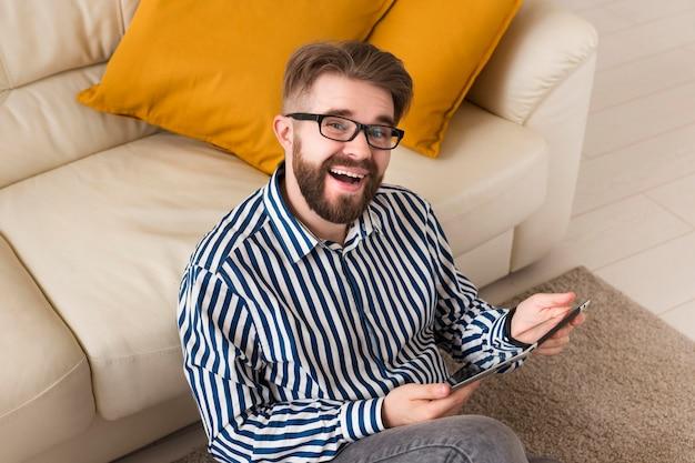 Wysoki kąt szczęśliwy człowiek w domu z tabletem