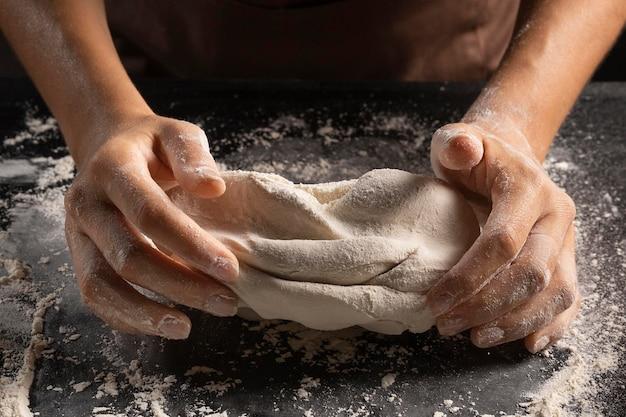 Wysoki kąt szefa kuchni wyrabiania ciasta rękami