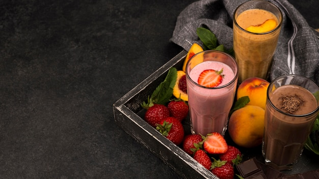 Wysoki kąt szklanek milkshake na tacy z czekoladą i owocami