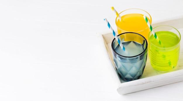 Wysoki kąt szklanek z napojami bezalkoholowymi i miejscem na kopię