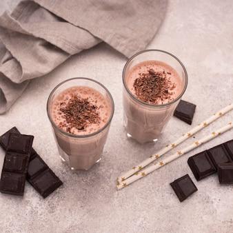 Wysoki kąt szklanki czekoladowych koktajli mlecznych ze słomkami