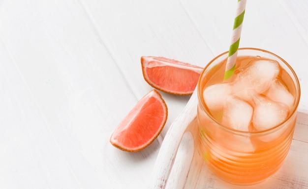 Wysoki kąt szklanki z napojem bezalkoholowym i grejpfrutem