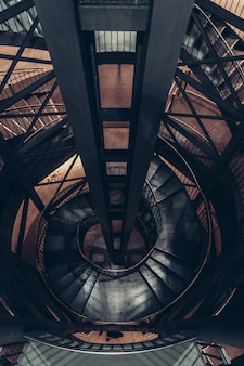 Wysoki kąt szybu windy w ciemnym starym budynku ze spiralnymi schodami