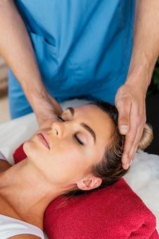 Wysoki kąt terapeuty osteopatycznego badającego kręgosłup szyjny pacjentki