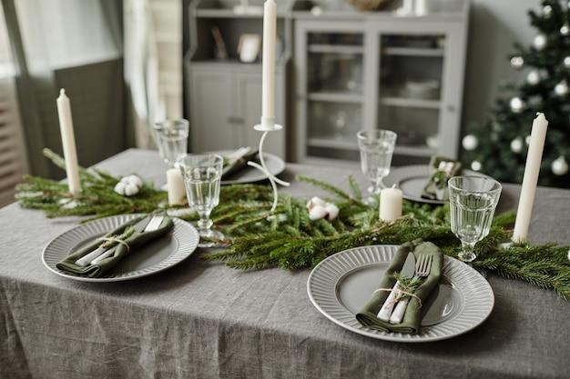 Wysoki kąt tła stołu w jadalni ozdobionego na boże narodzenie gałęziami jodły i ...